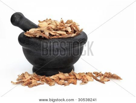 Licorice root used in traditional chinese herbal medicine in a black granite mortar with pestle isolated over white background. Gan cao.