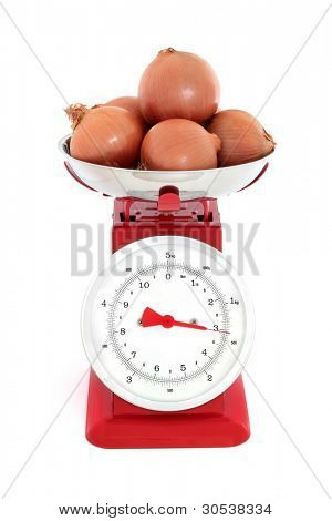 Onion vegetables weighing three kilos on a red metal set of retro scales against white background.