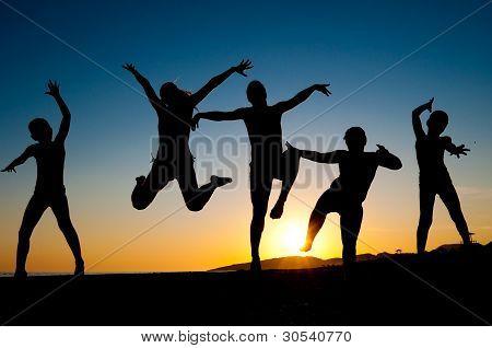 Silhuetas de crianças felizes pulando na praia