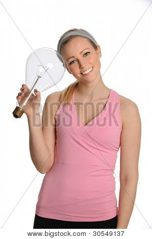 Beautiful young woman holding large incandescent light bulb isolated over white background