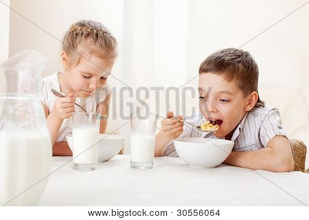 Children eat breakfast. Family eating cereals with milk