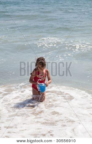 Niña jugando con un cubo en la playa