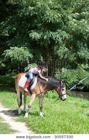 Niña, acariciar a un caballo mientras que monta a caballo