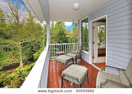 Balcony With Outdoor Furniture And View Of Woods And River.