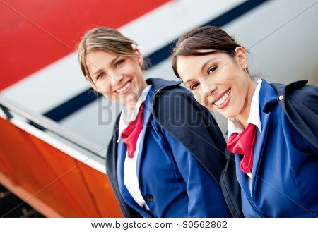 Friendly air hostesses smiling and welcoming into the airplane