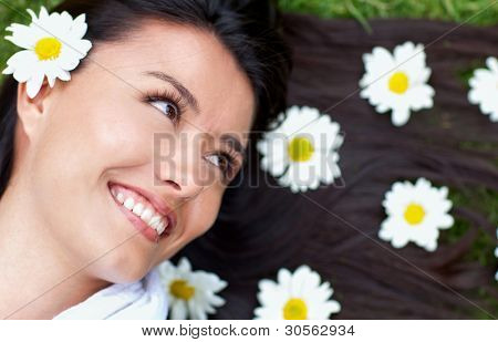 Gorgeous woman portrait lying in a garden of daisies