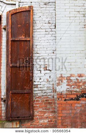 Old weathered and rusted shutter against a white painted red brick wall