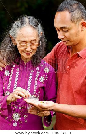 Asian Young Man Help Elderly Mother Taking Medicine
