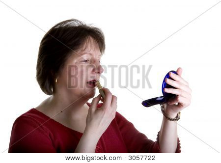 Woman In Red Putting On Lipstick
