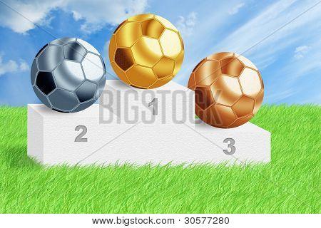 Pelotas de fútbol en podio entre la hierba verde.