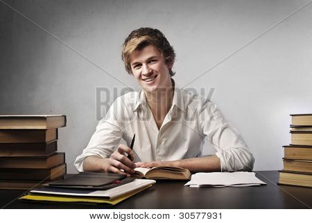 Smiling young student surrounded by books