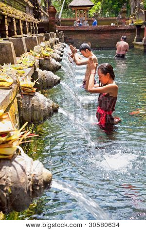 TAMPAK SIRING, BALI, INDONESIA - JANUARY 26: People praying at holy spring water temple Pura Tirtha Empul during purification ceremony on January 26, 2011 in Tampak Siring, Bali, Indonesia