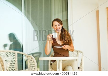 Smiling Girl Having Cup Of Coffee At Terrace