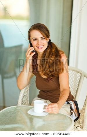 Happy Young Woman Speaking Cell Phone And Having Cup Of Coffee A