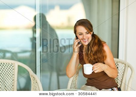 Happy Girl Speaking Cell Phone And Having Cup Of Coffee At Terrace