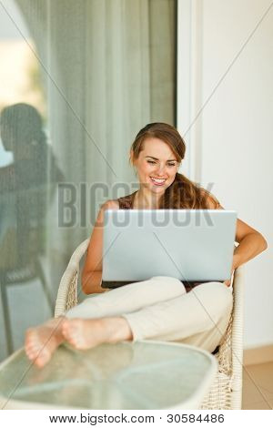 Smiling Young Woman Relaxing On Terrace With Laptop
