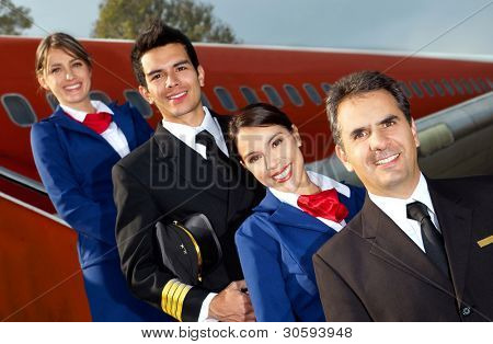 Friendly cabin crew smiling with an airplane at the background