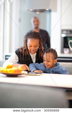 Kitchen setting with young black family playing with a tablet pc.