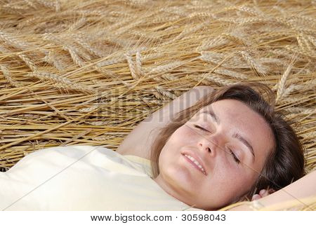 Young woman lies in golden grain
