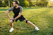 Portrait of energetic sporty man with fitness body stretching his body with expander equipment durin poster