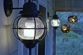 image of screen-porch  - Pair of exterior compact fluorescent electric light fixtures on screened porch - JPG