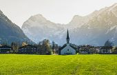 Small Village Under Alps Mountains Landscape.. Alpine Landscape With Small Church. Morning Landscape poster