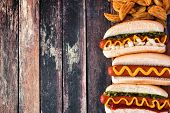 Hot Dogs With Toppings And Potato Wedges. Side Border, Top View On A Dark Wood Background With Copy  poster
