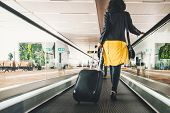 Woman Traveller With Travel Suitcase Or Luggage Walking In Airport Terminal Walkway For Vacation Tra poster
