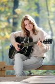 picture of teenage girl  - Young Caucasian girl in forest with guitar selective focus - JPG