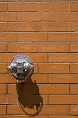 pic of firehose  - Dry standpipe on brick wall with peeling chrome coating - JPG