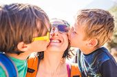 Children Kiss Mom. A Woman Hugs Her Sons And Smiles. The Boy Hugs Mother And Brother. Happy Motherho poster