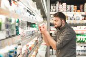Funny Man With A Beard Is In The Milk Department Of The Supermarket Near The Shelves Of Yogurt, Hold poster