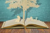 picture of paper cut out  - Paper cut of children read a book under tree on old book - JPG