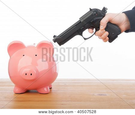 Man Pointing A Gun At A Piggy Bank