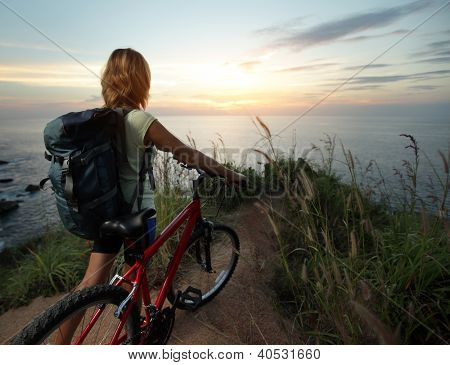 Rider with backpack standing on top of a hill with mountain bike and enjoying the sunset sea view