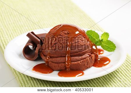 chocolate ice cream sundae topped with liquid caramel and decorated with chocolate curls