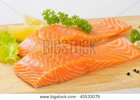 two salmon steaks on the wooden cutting board