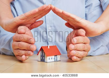 Four hands as a protecting roof over a little house