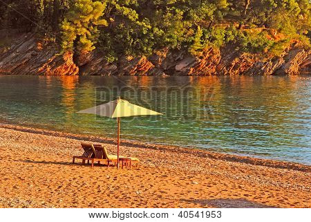 Two Deck Chairs And Umbrella On The Beach .