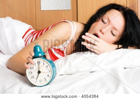 Young Woman Waking Up And Yawning In The Morning
