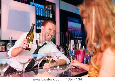 Young woman in club or bar drinking champagne and is flirting with the barkeeper