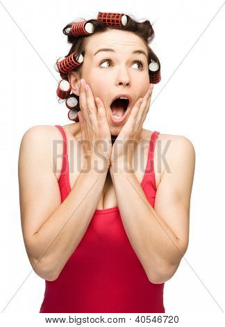 Young woman is holding her face in astonishment while wearing hair-rollers, isolated over white