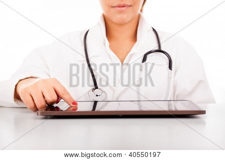 Female doctor with tablet computer at the desk, isolated over white background.