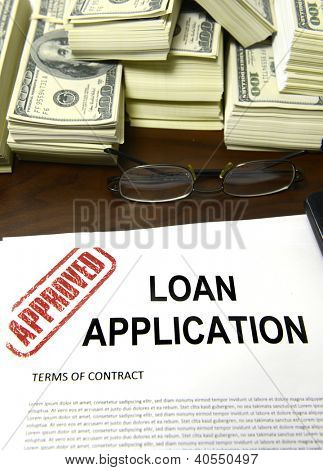 Approved loan application and dollar bills on desk