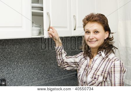 Woman Opens A Cupboard