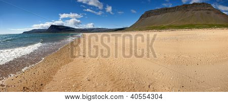 Beach under the mighty fjords rising from the sea in the Westfjords Peninsula, northwestern Iceland