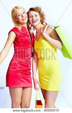 Dois compradores bonitos com paperbags sobre fundo branco