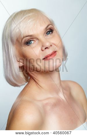 Side view of a nude senior lady looking at camera with a charming smile