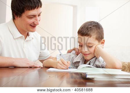 Father helping son do homework. Parent helps his child