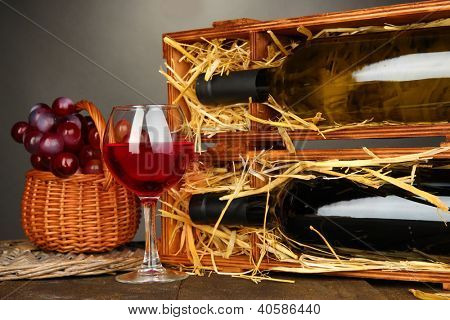 Wooden case with wine bottles, wineglass and grape on wooden table on grey background